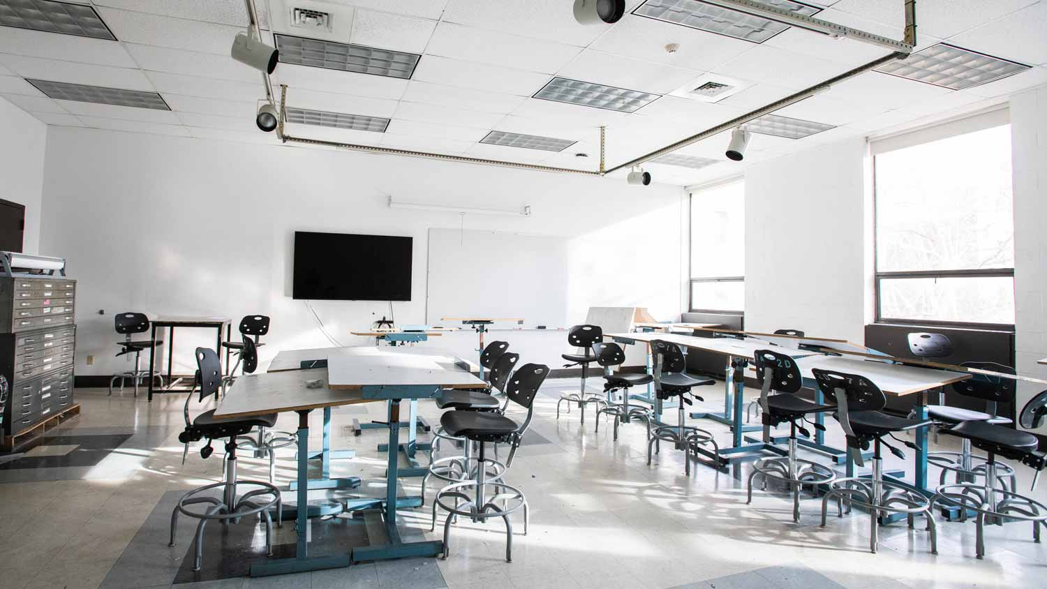 White lab room with 2 rows of desks with chairs