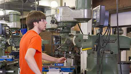 Student in an orange shirt working with a drill press