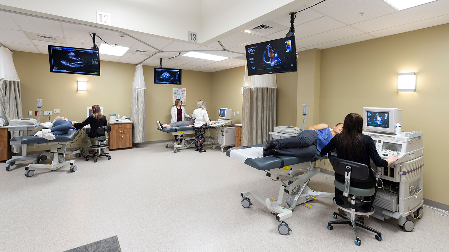 a hospital room with 3 patients all using ultrasound scanners with TVs on the wall showing the scan imagery
