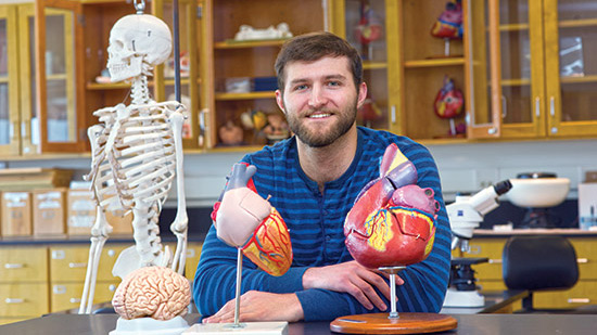 Student sits in lab with models of brain, heart and human skeleton