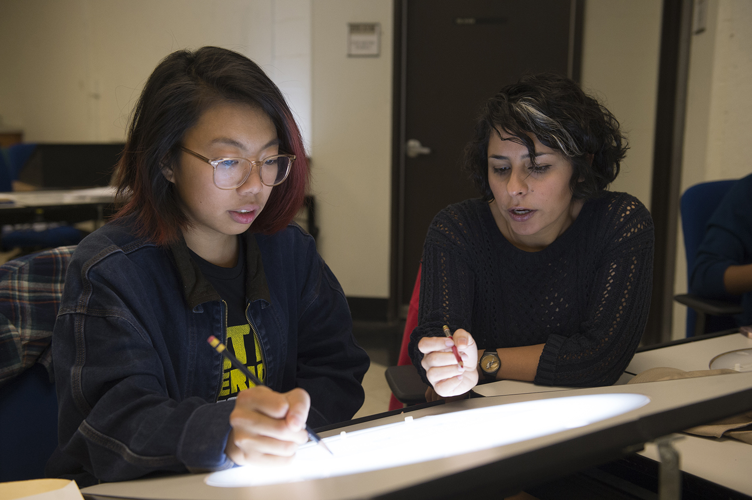 A student works with a faculty member in the Animation Classroom.