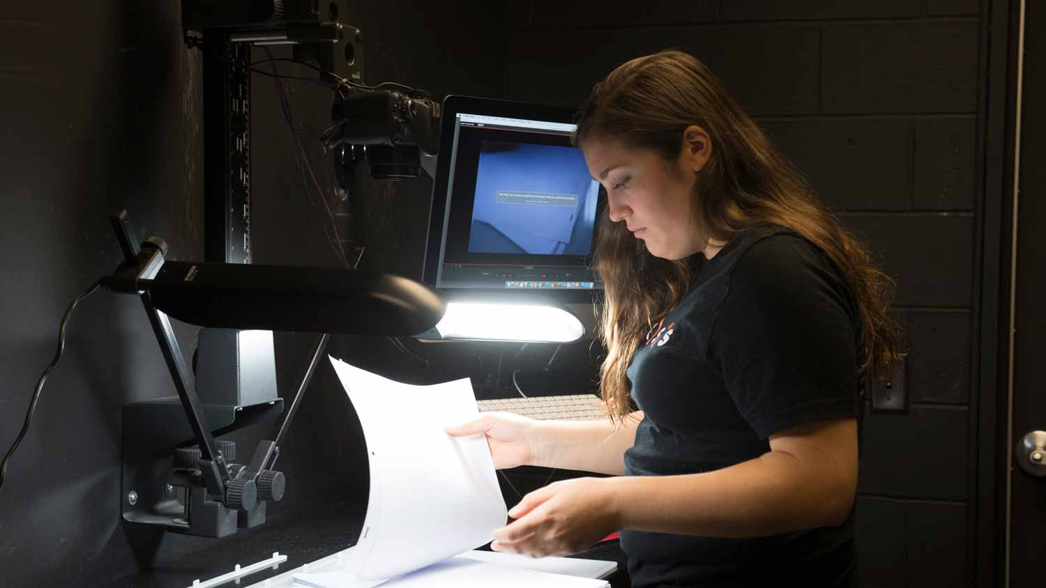 Female student reviewing a script in the Animation Crane Room