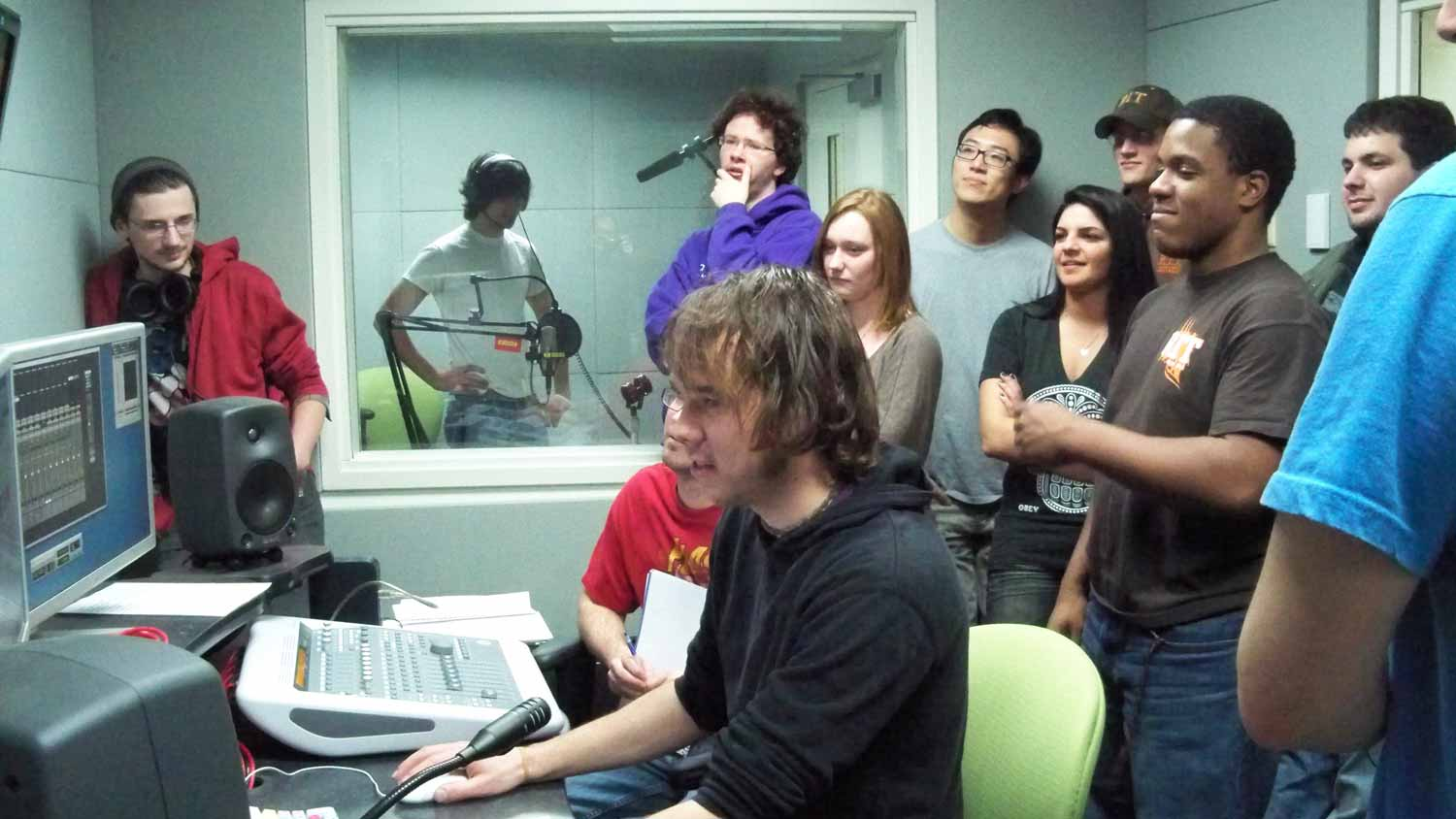 A group of students recording in the audio control room
