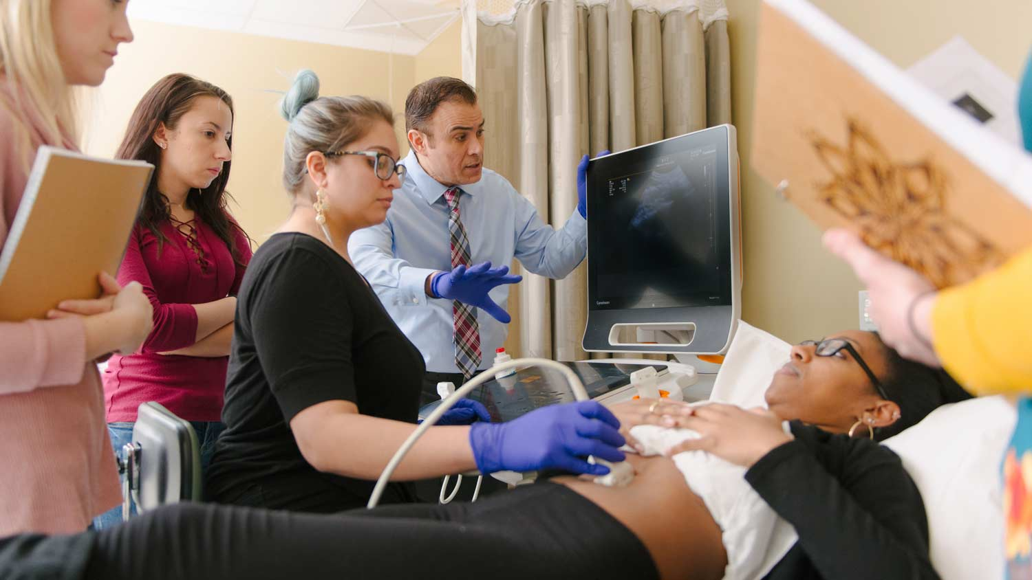 A group of people performing a sonogram on a patient
