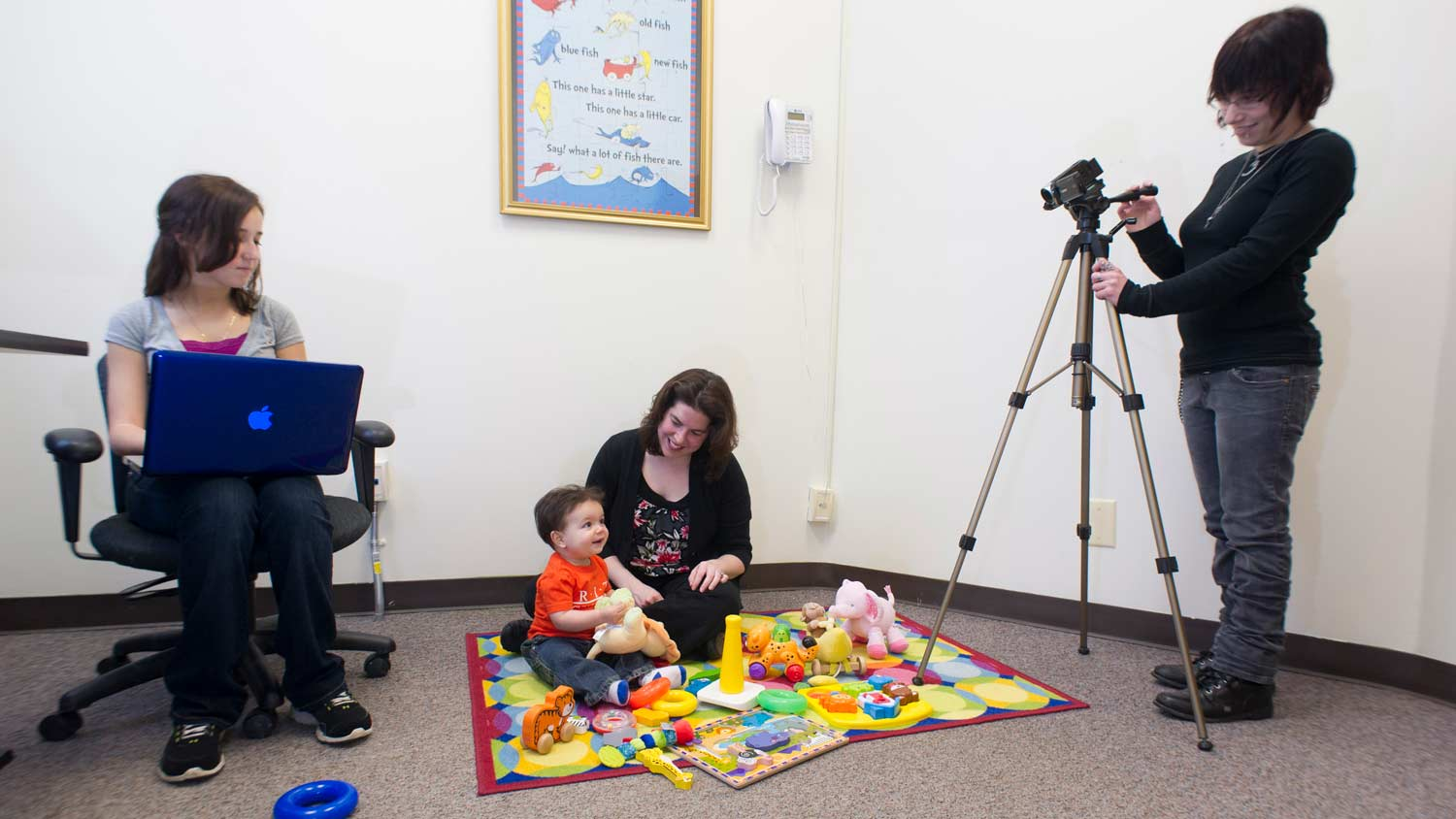 Two people recording a baby playing on a play mat with another adult