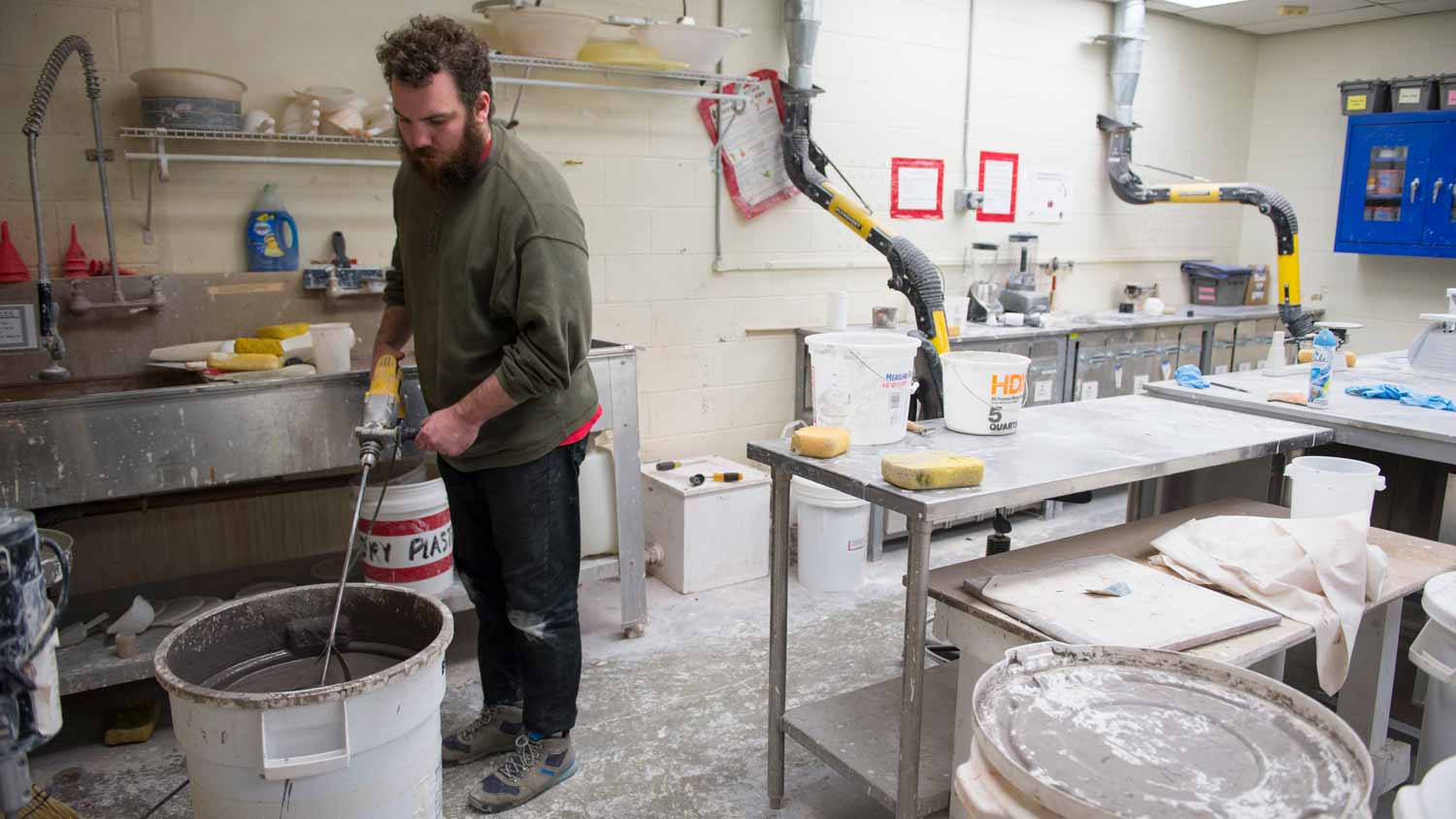Student using a drill to mix in the clay and glaze formulation and spray booth room