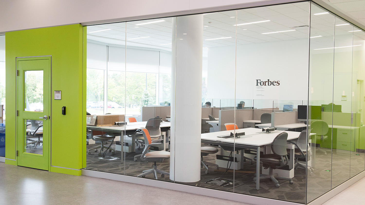 Glass room with lime-green door and several workstations with tables and chairs