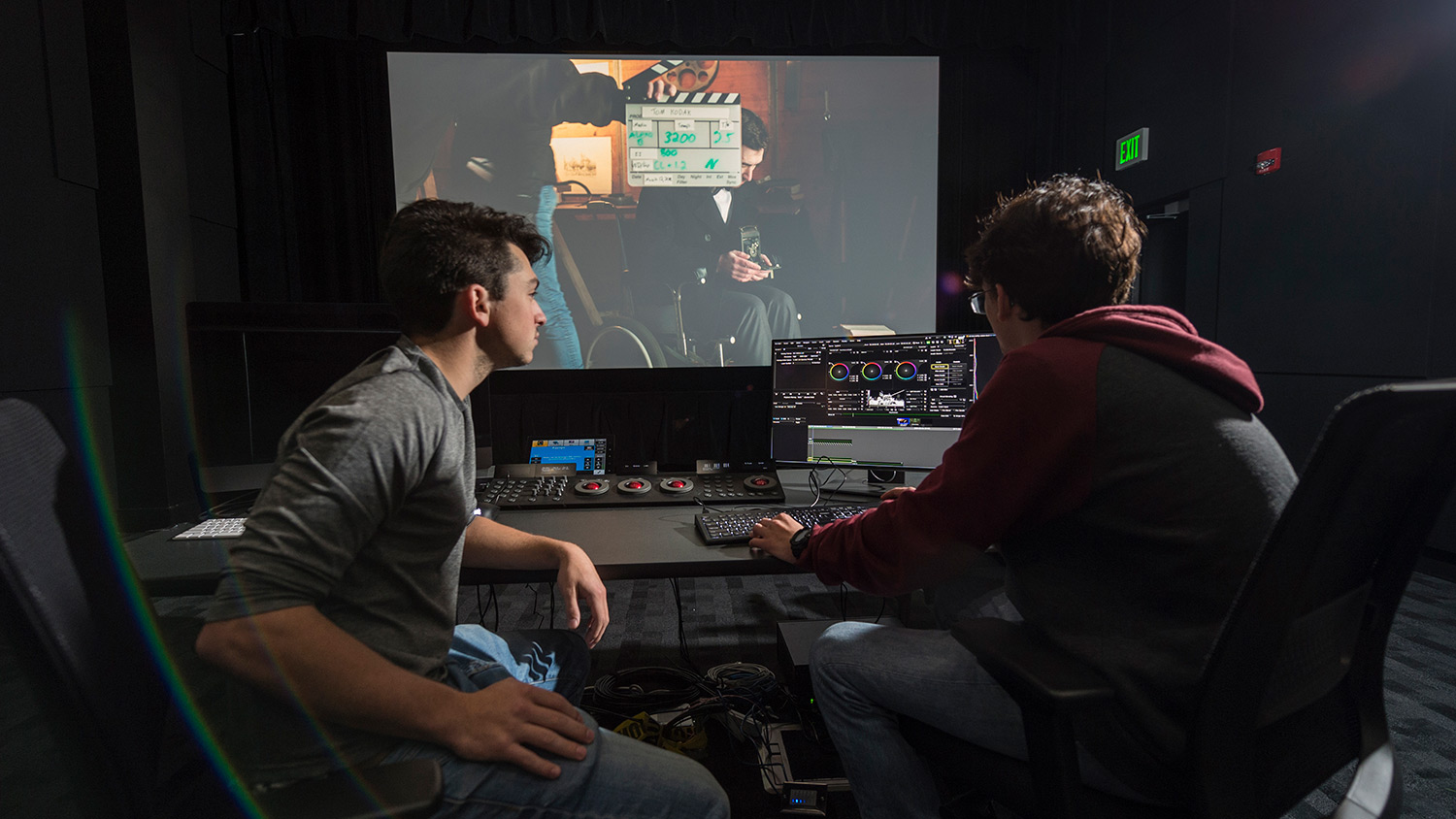 Two students sit in dark room in front of controls as screen plays movie in background