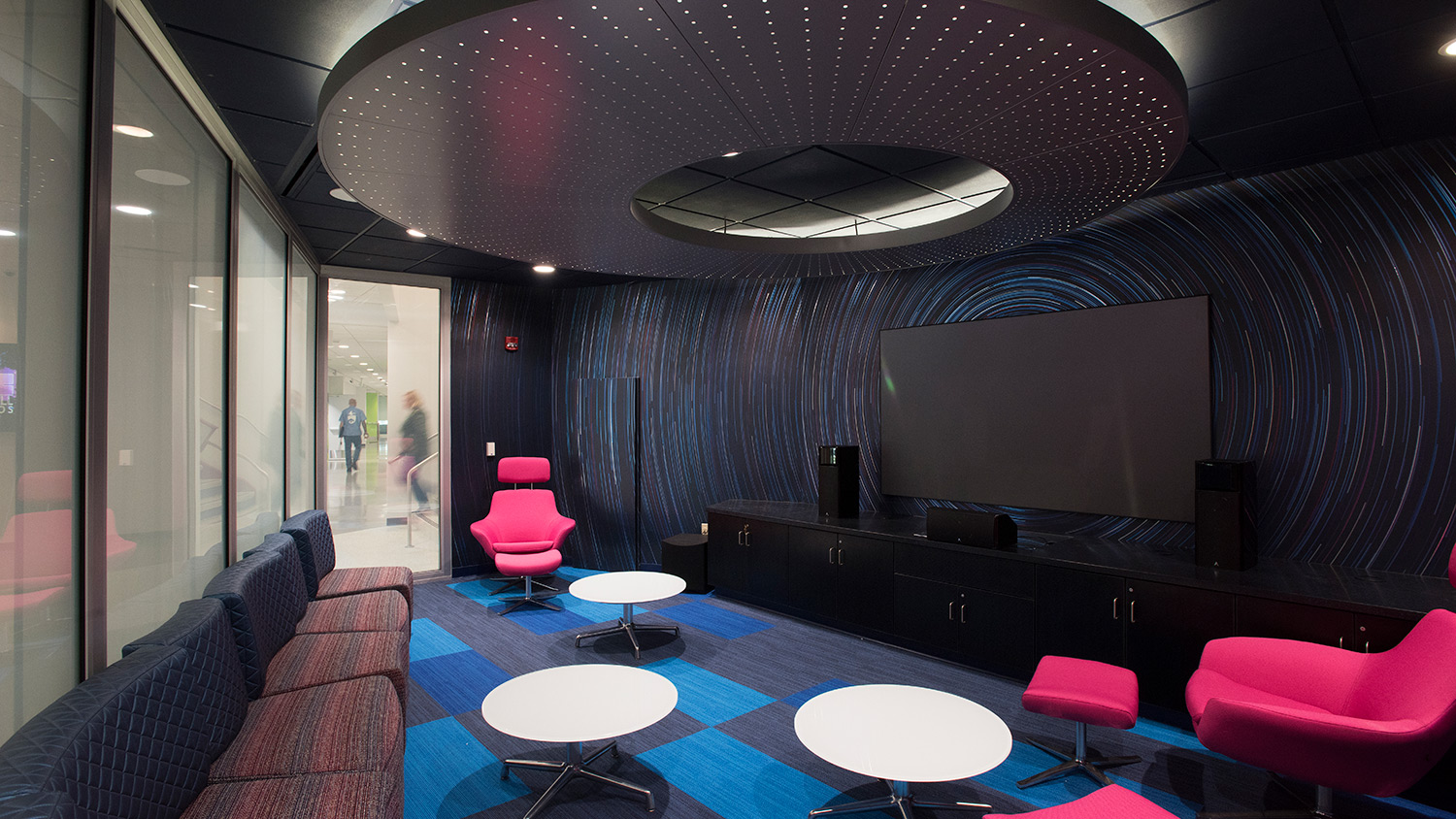 Dark room with white circular tables, hot pink chairs and large TV screen with speakers