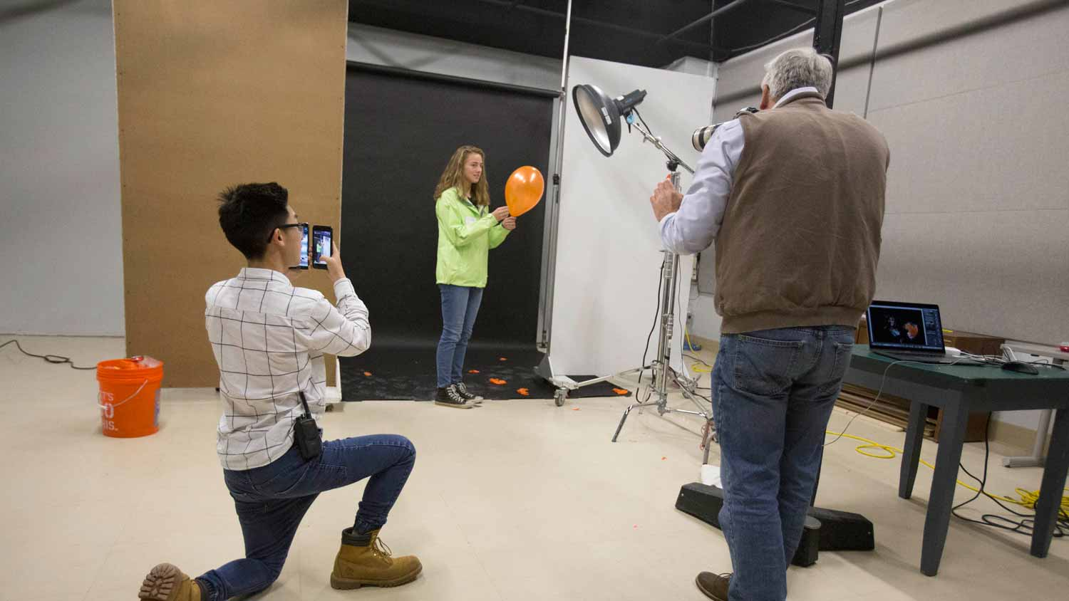 3 people capturing a balloon pop with video equipment