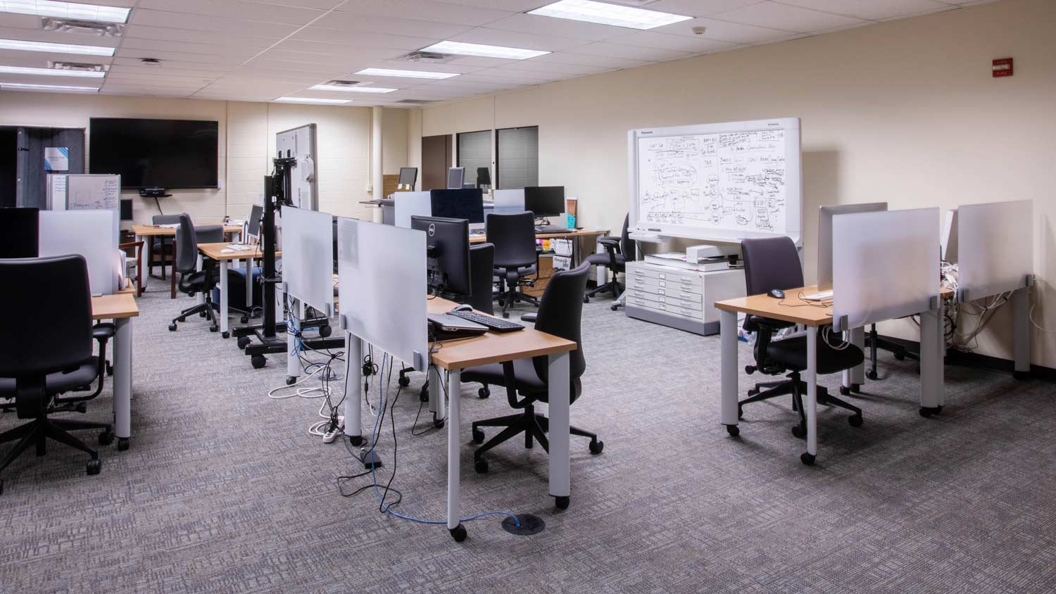 Sectioned off computer lab with different work stations spread out throughout the room