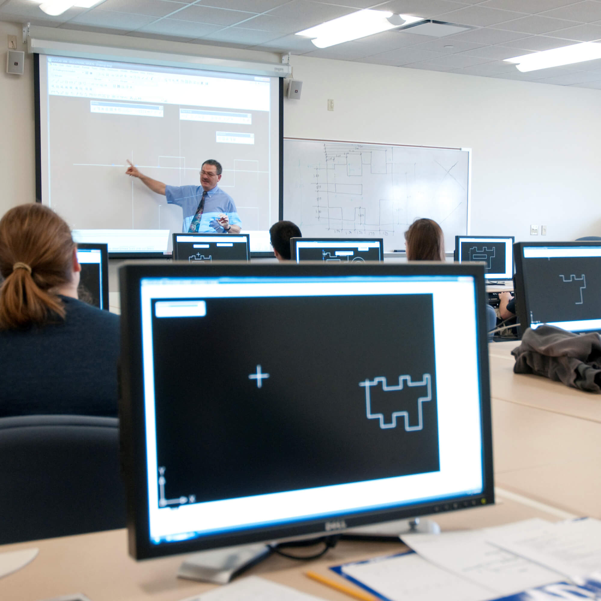 Interior view of the Design and Drafting Lab, showing students working at computers.