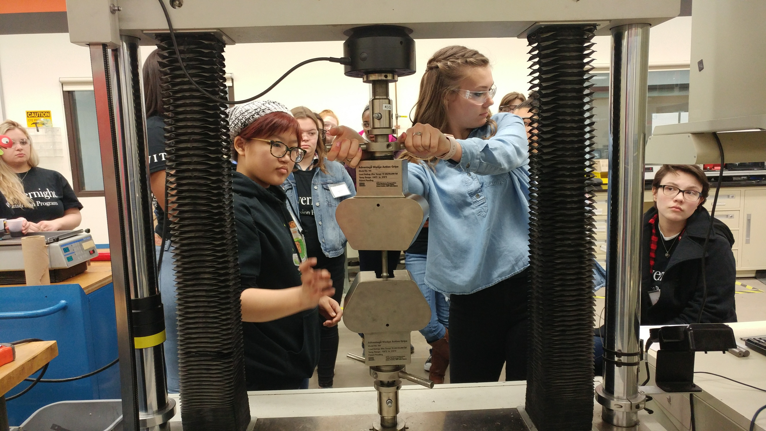 A group of students work with a large piece of lab equipment
