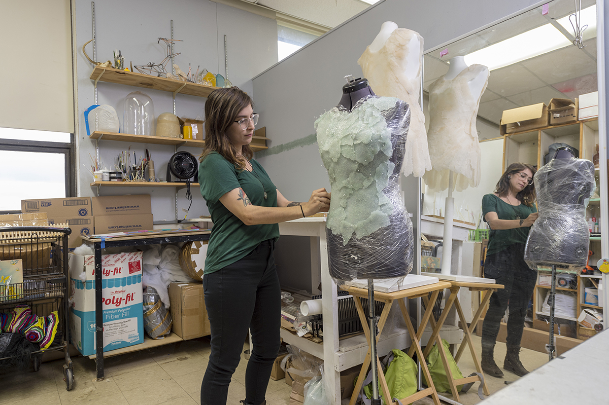 Gracia Nash '19 MFA puts some touches on a project in the glass workspace. Photo by Elizabeth Lamark.