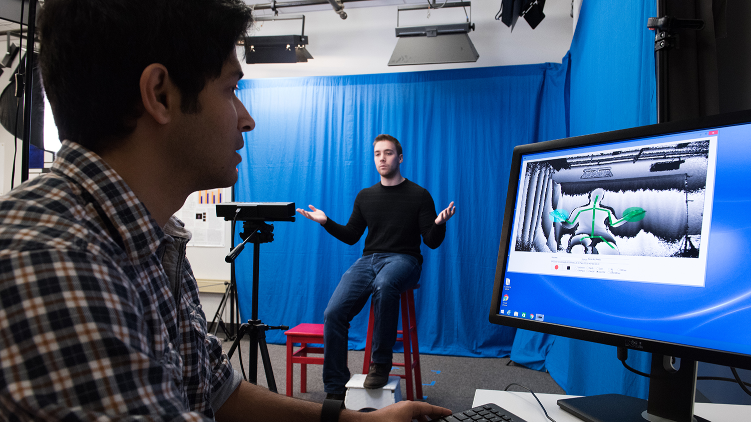 Image showcasing a person using ASL which is being recorded and monitored by another individual on a computer with a camera and interpretive software.