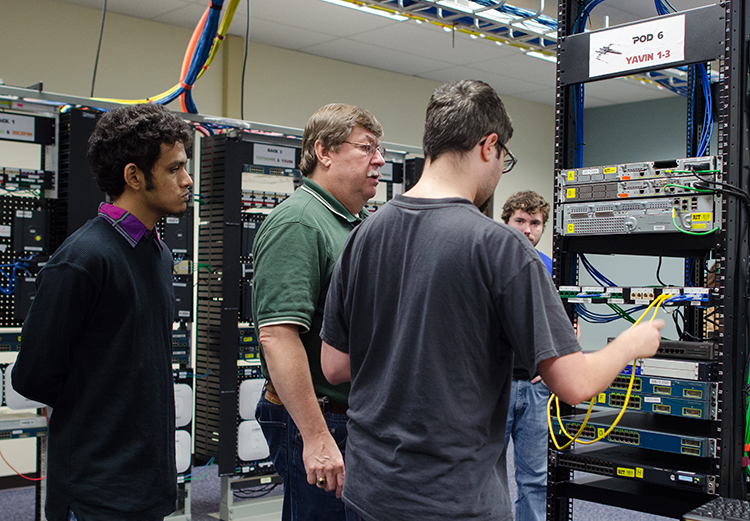 Students and a professor from the School of Information working on a deck in the Systems and Administration Lab.