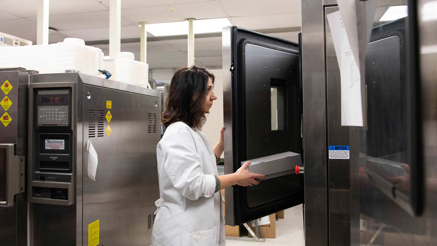 Woman in a lab coat putting a box into a large metal machine