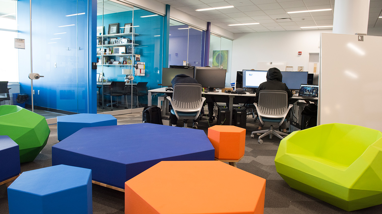 Open room with colorful, hexagonal seats and tables with desktop computers