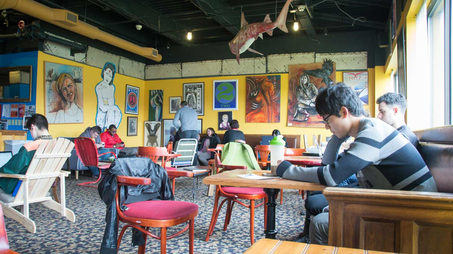 An artistic cafe with people enjoying coffee and drinks