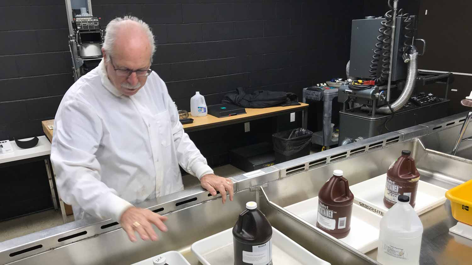 A man wearing a white coat looking at image development chemicals in a long sink with black walls in the background