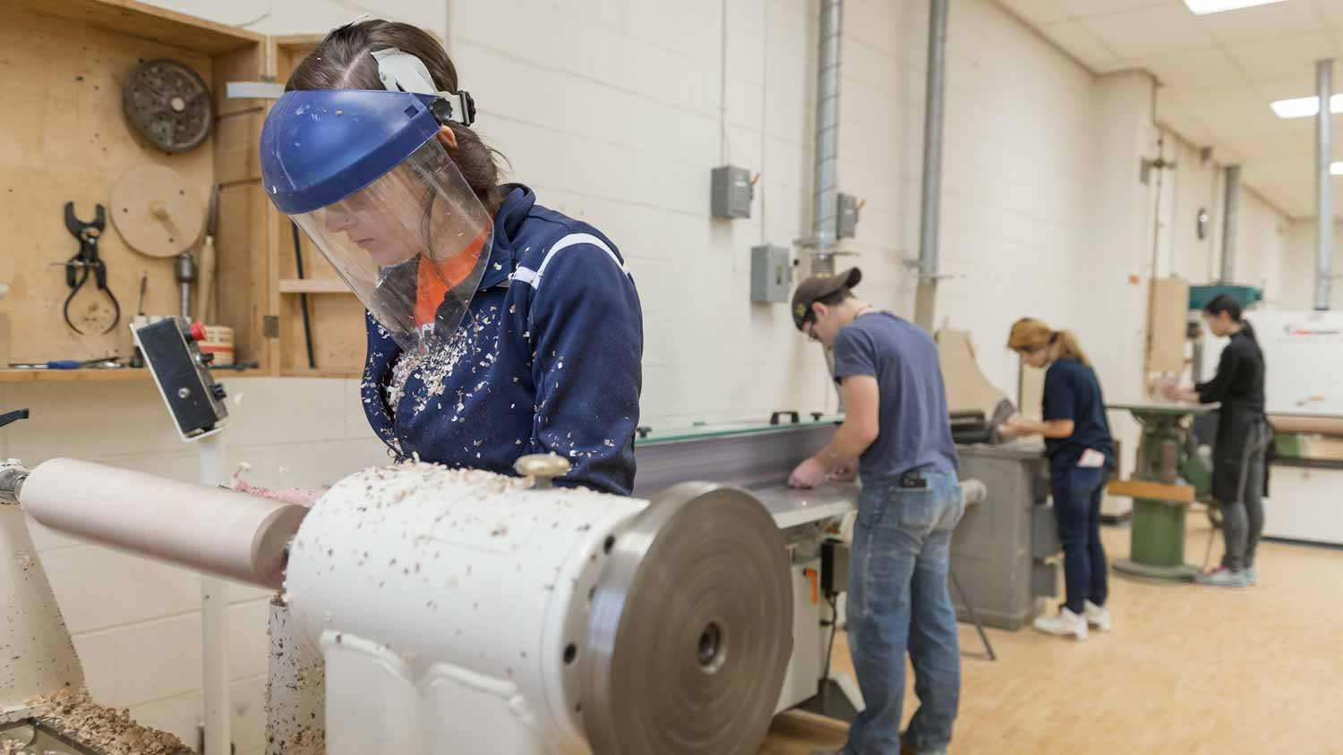 Female wearing a protective mask turning a piece of wood on a lathe