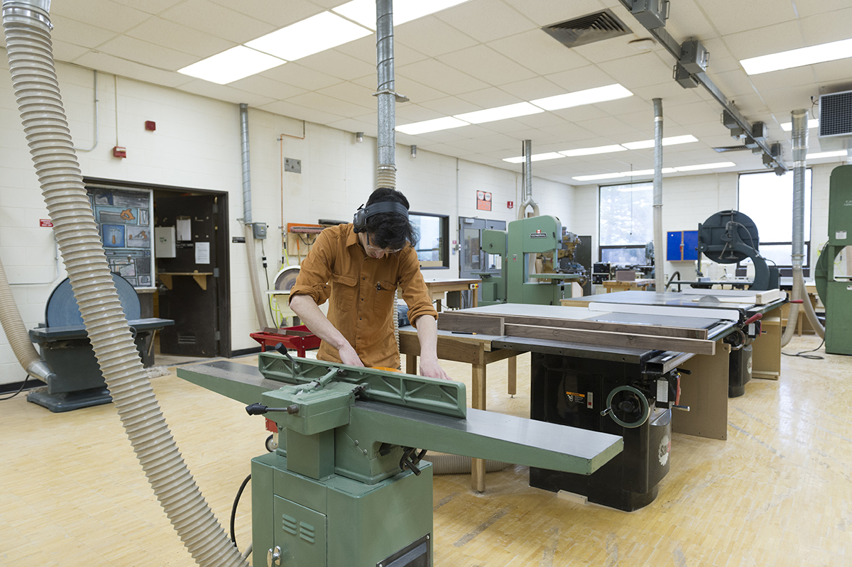 A wide shot of a student working in the furniture design machine room.