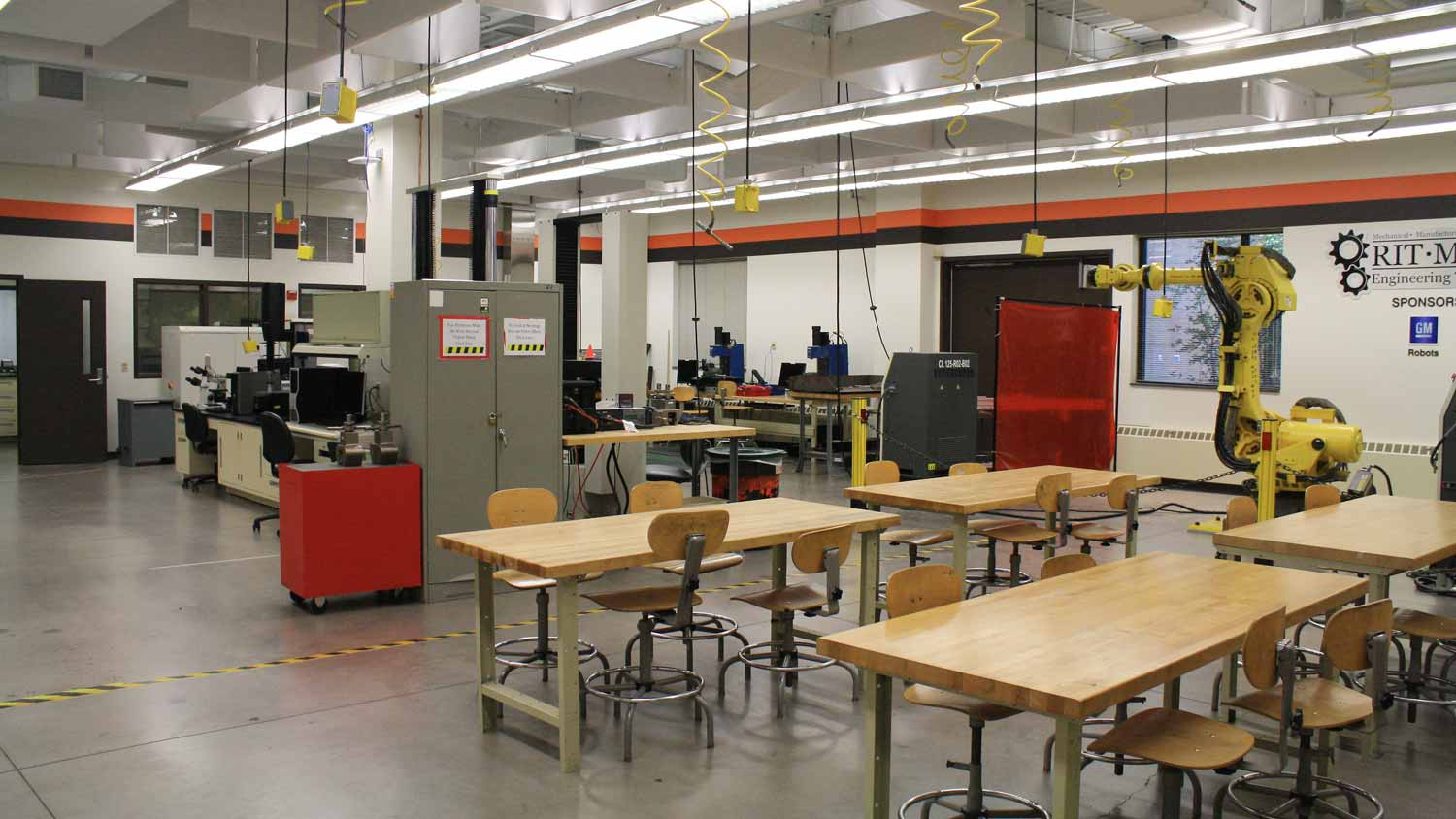 Four tables in a workspace with a robotic arm and other machines