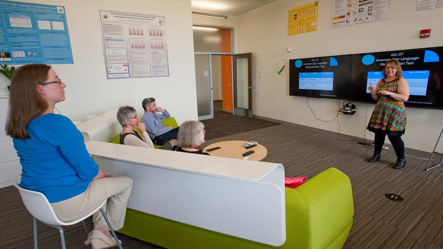 People on a couch watching a presentation on two televisions