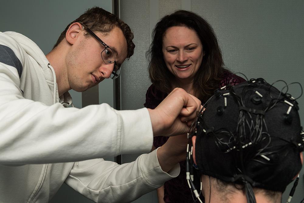 Dr. Houston supervising student using EEG equipment