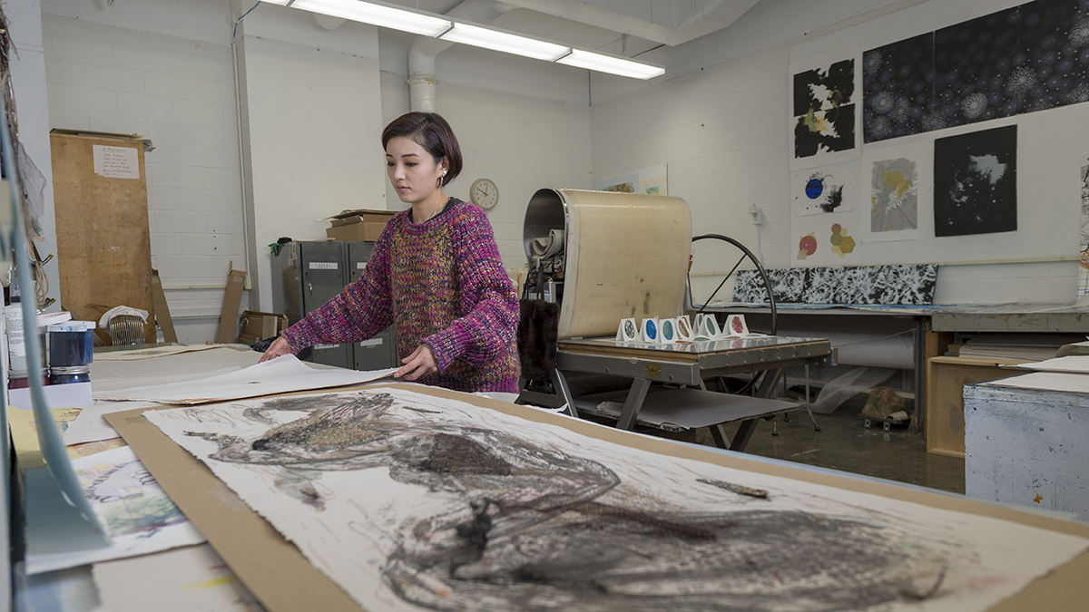A graduate student works on a project in the Printmaking Studio.