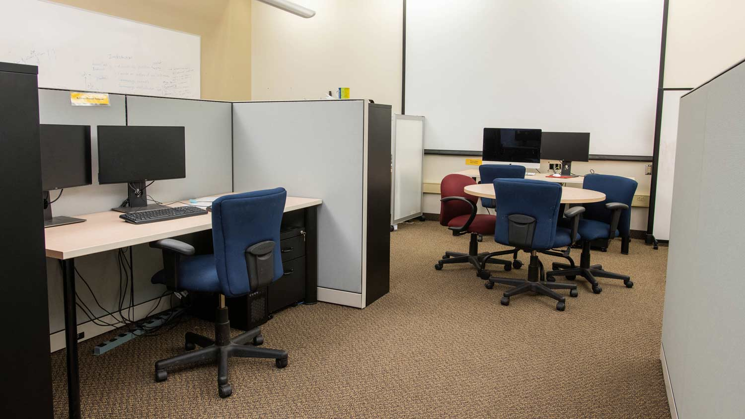 Cubicles with computer workstations and a small round table