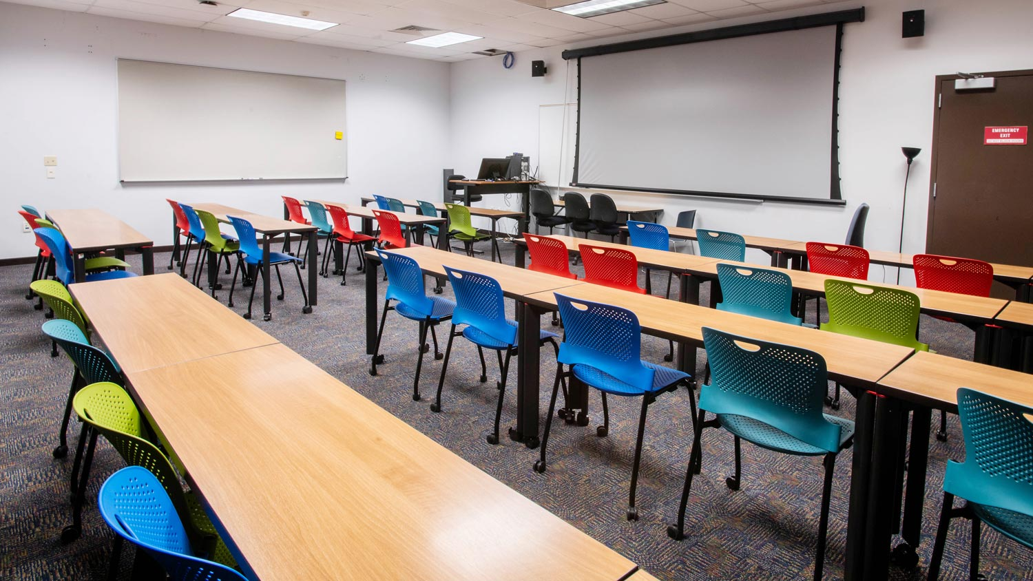 Row of desks in a classroom with colorful chairs