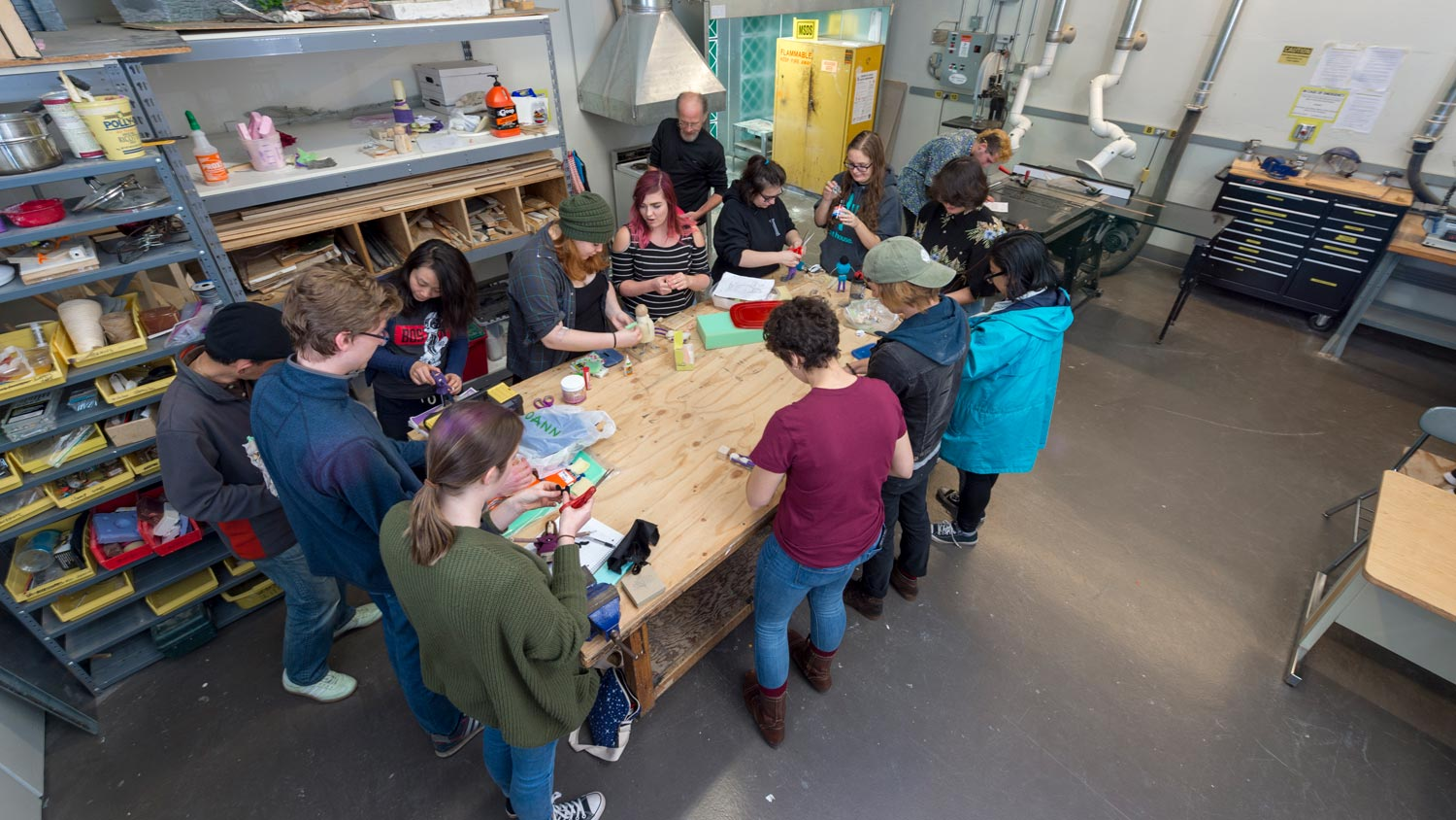 Group of students standing around a workbench painting props