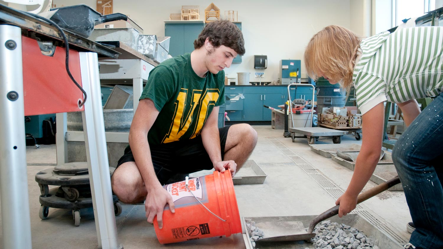 Two students scooping small stones into a 5 gallon bucket