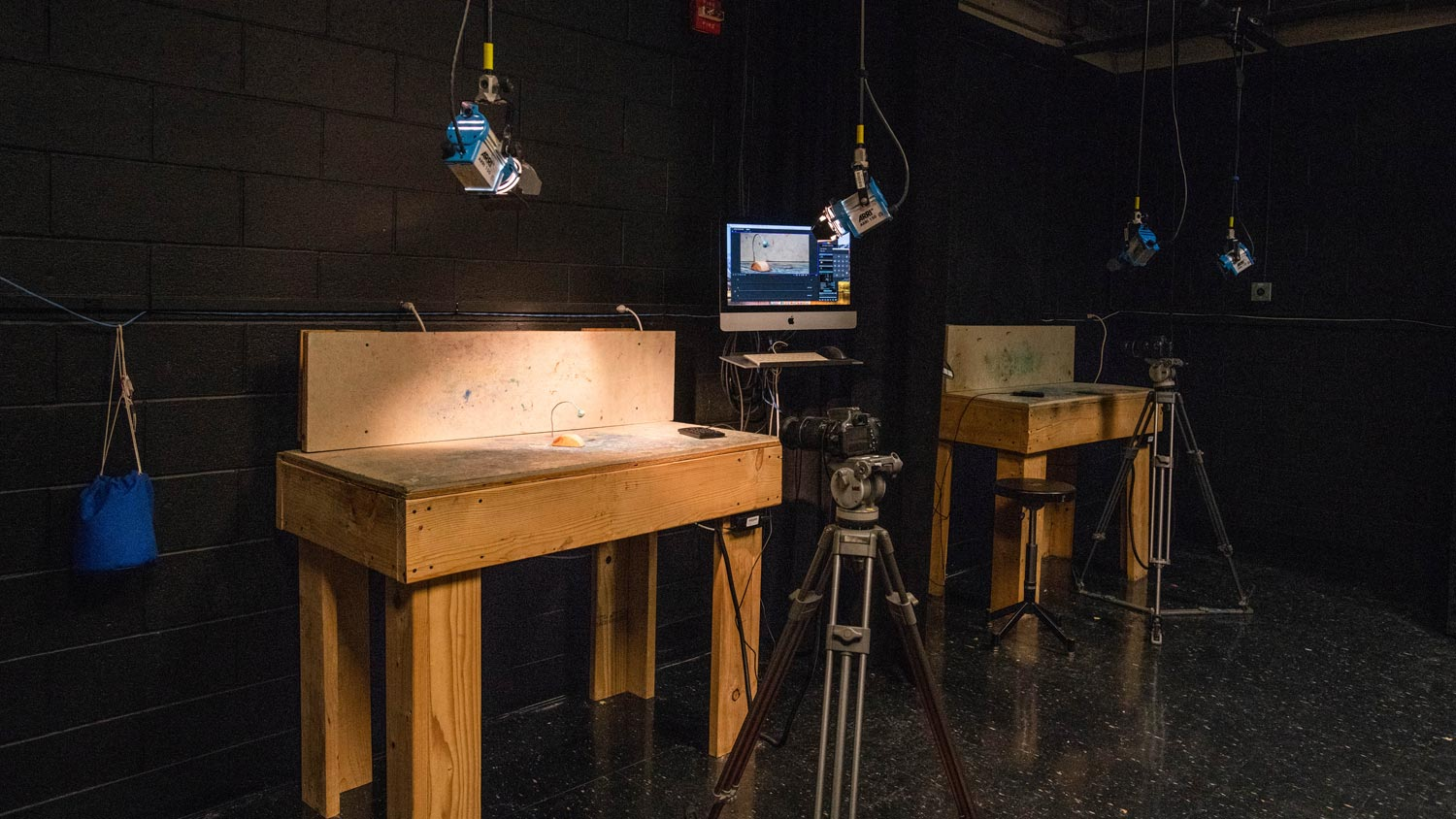 Stop motion film set in a black room with wooden stages and lights hanging from the ceiling