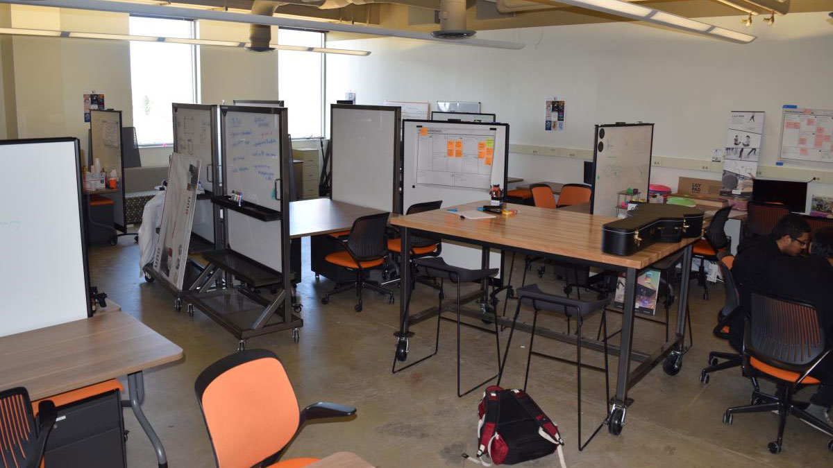 lab space with several tables and chairs, and whiteboards.