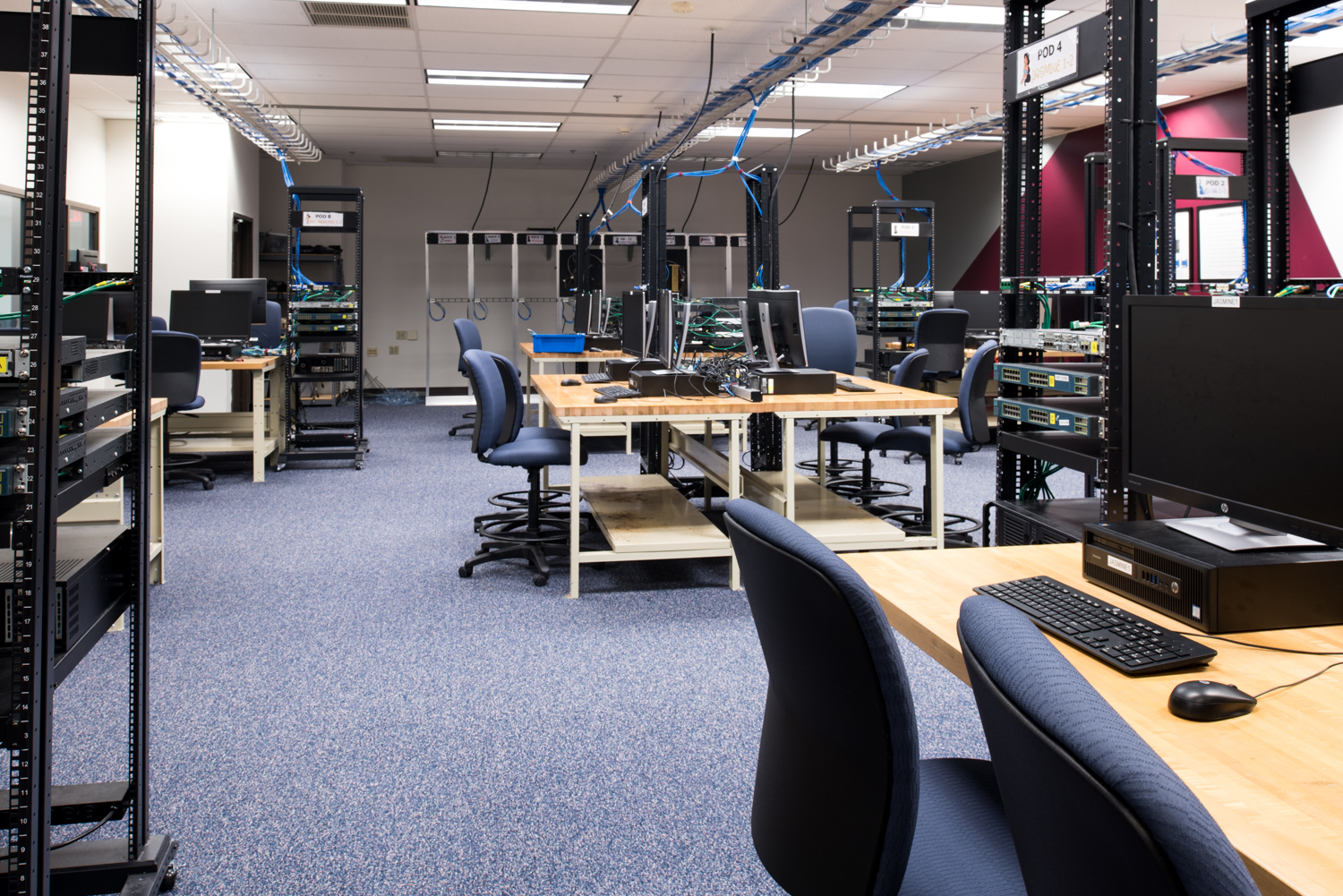 An image showcasing the Systems Administration Lab in the School of Information at RIT. It showcases the lab full of computers, racks, switches, routers and servers.