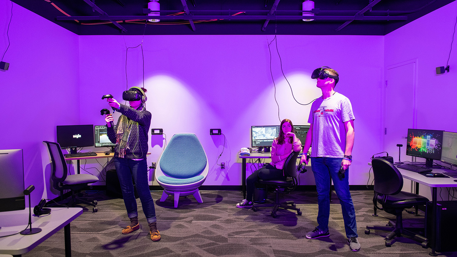 Two students stand wearing VR goggles and holding controllers in room with chairs and computers