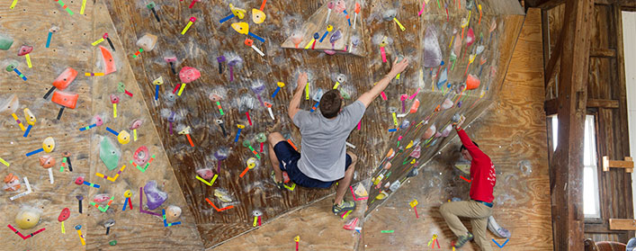 Two people hanging off of an indoor rock wall