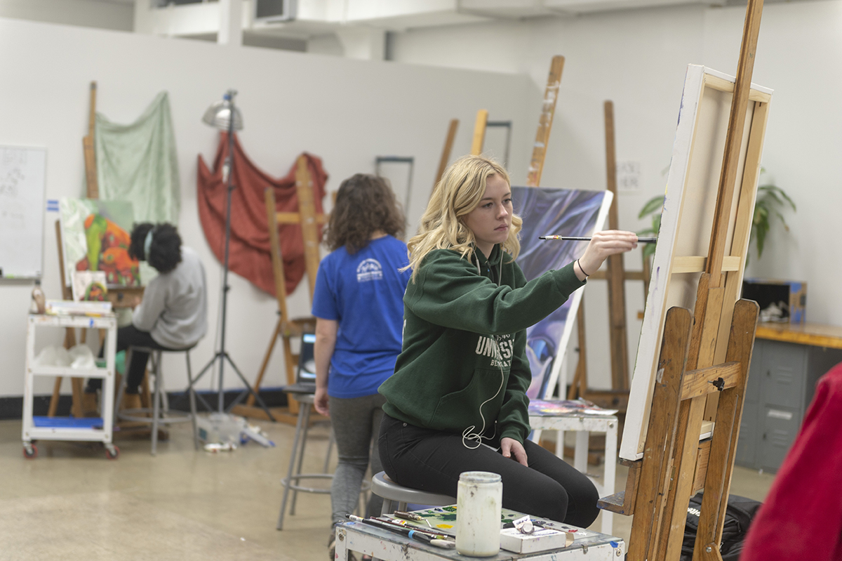 Students paint on canvas in a painting studio.