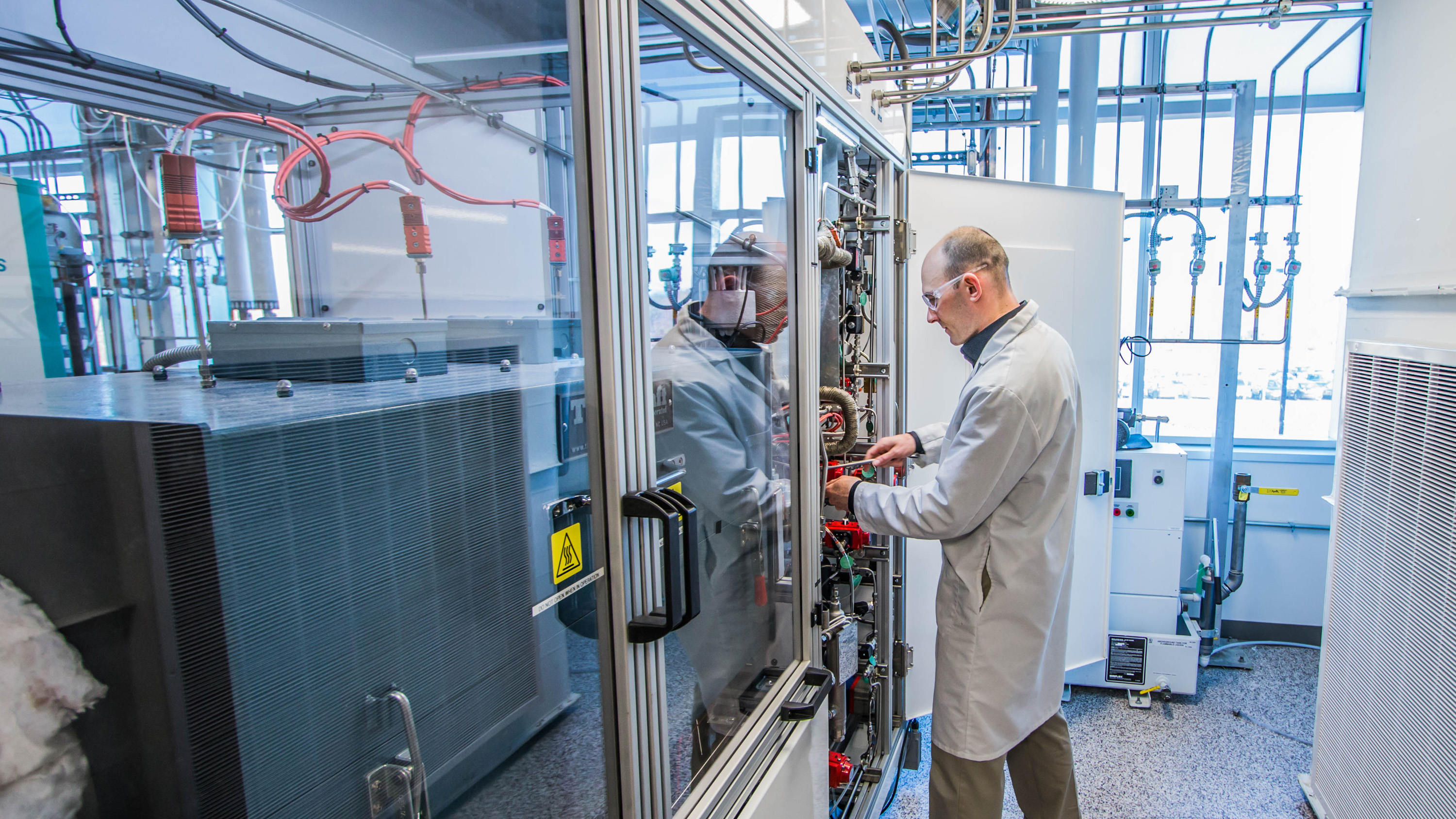 Man in lab coat working on a panel in a fuel cell lab