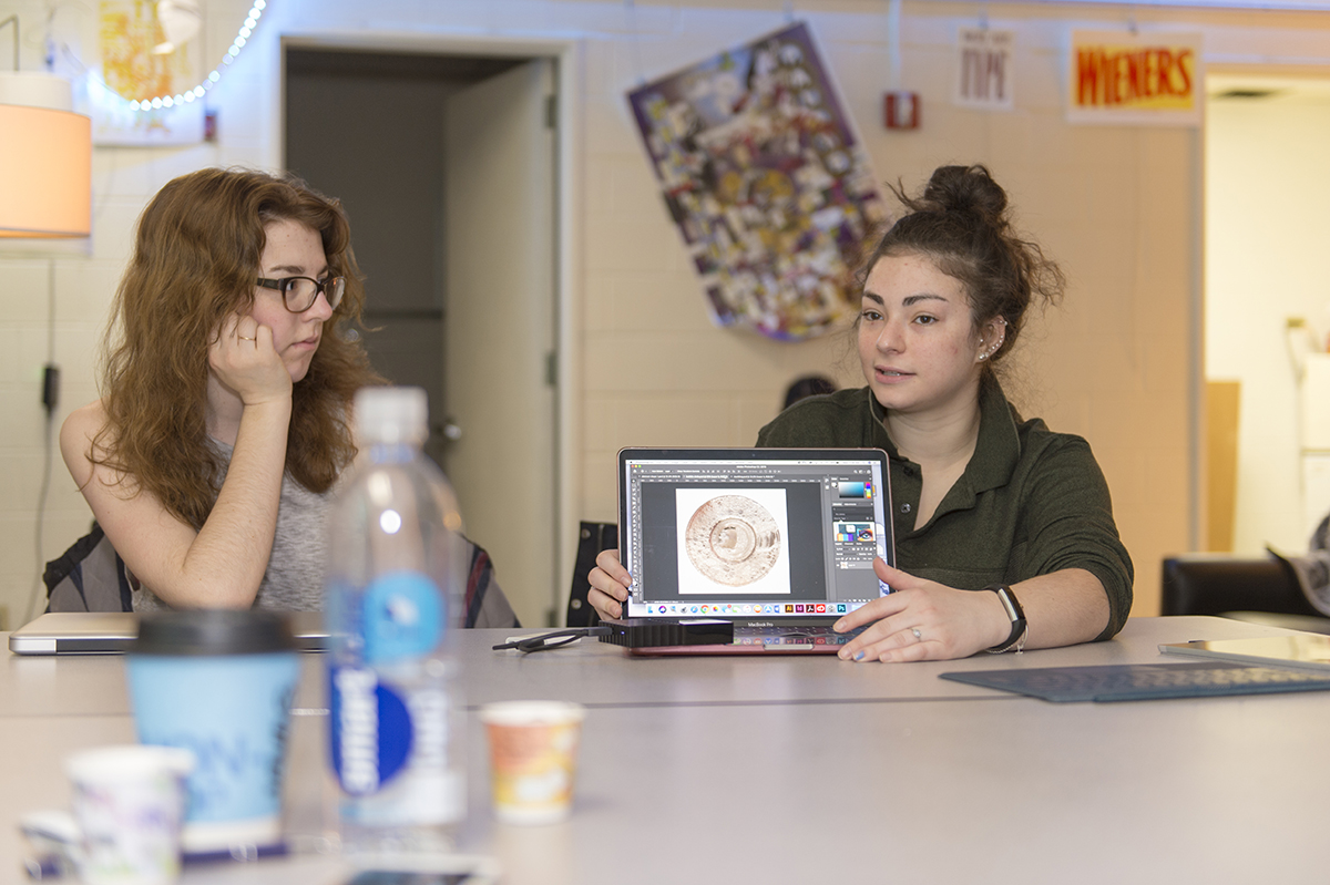 A student presents her laptop screen to a group.