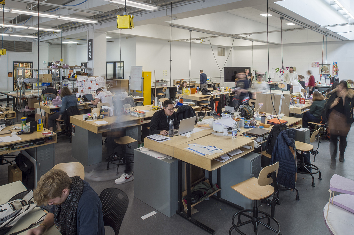 A wide shot of students working in the senior industrial design space.