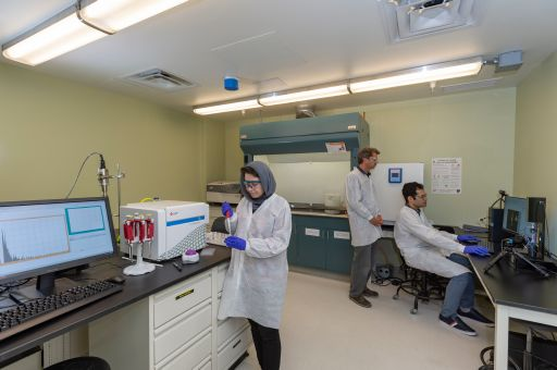 3 people in lab coats working in a lab