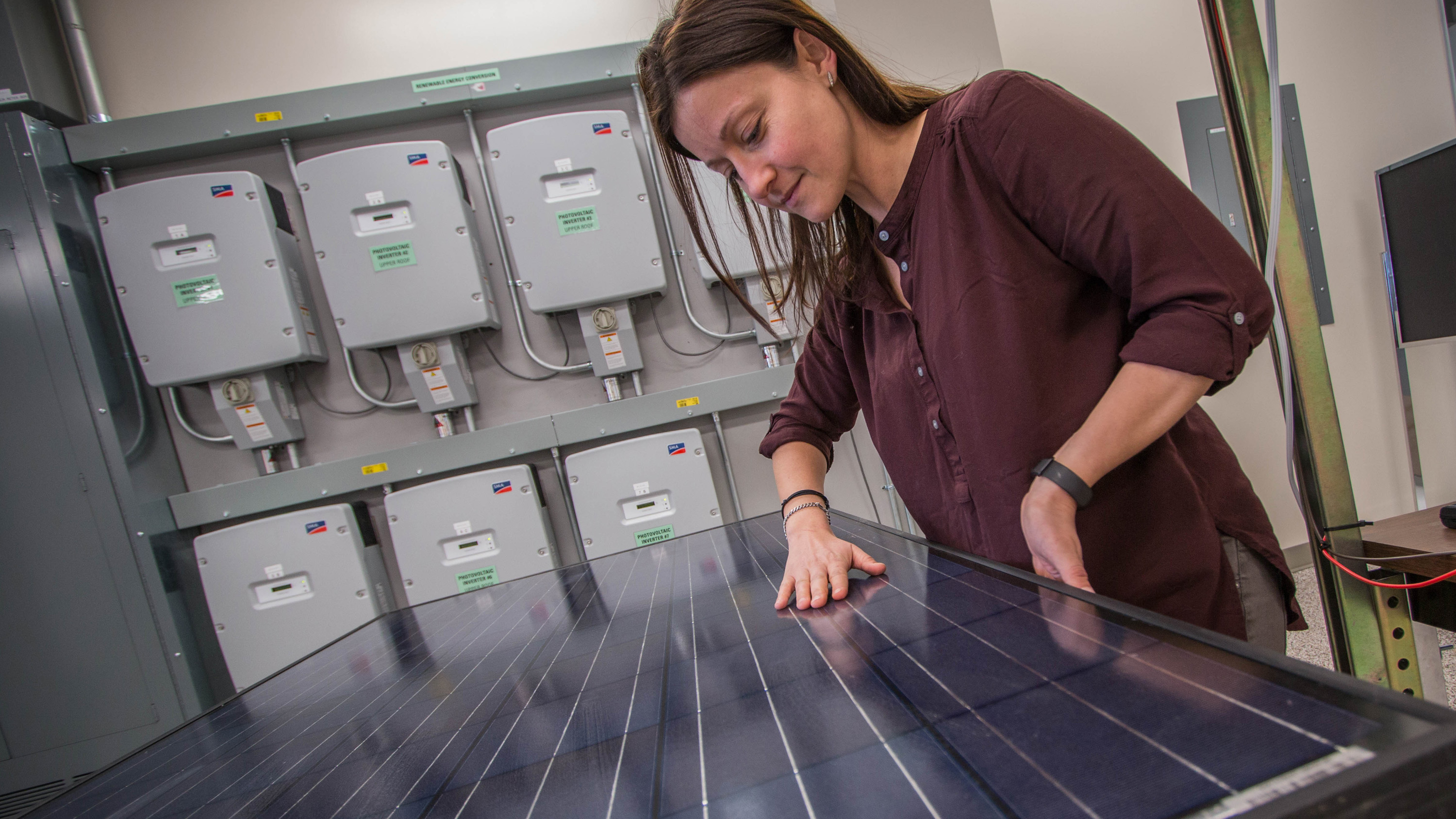 Woman with hands on a photovoltaic panel