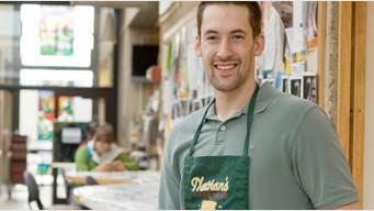 Man wearing a green shirt and a Nathan's bakery apron