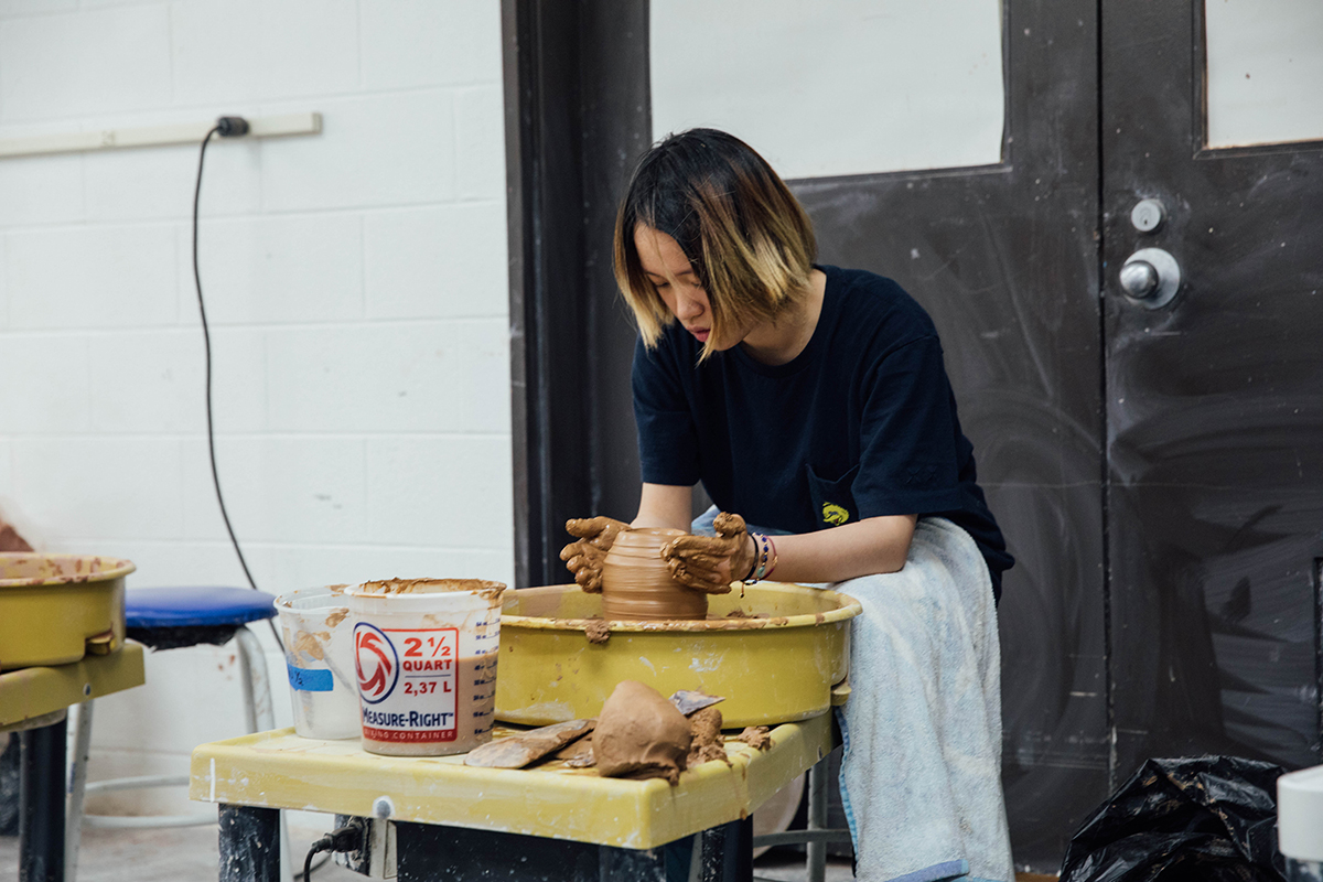 A female student spins clay on a wheel. Photo by Sam Kang.