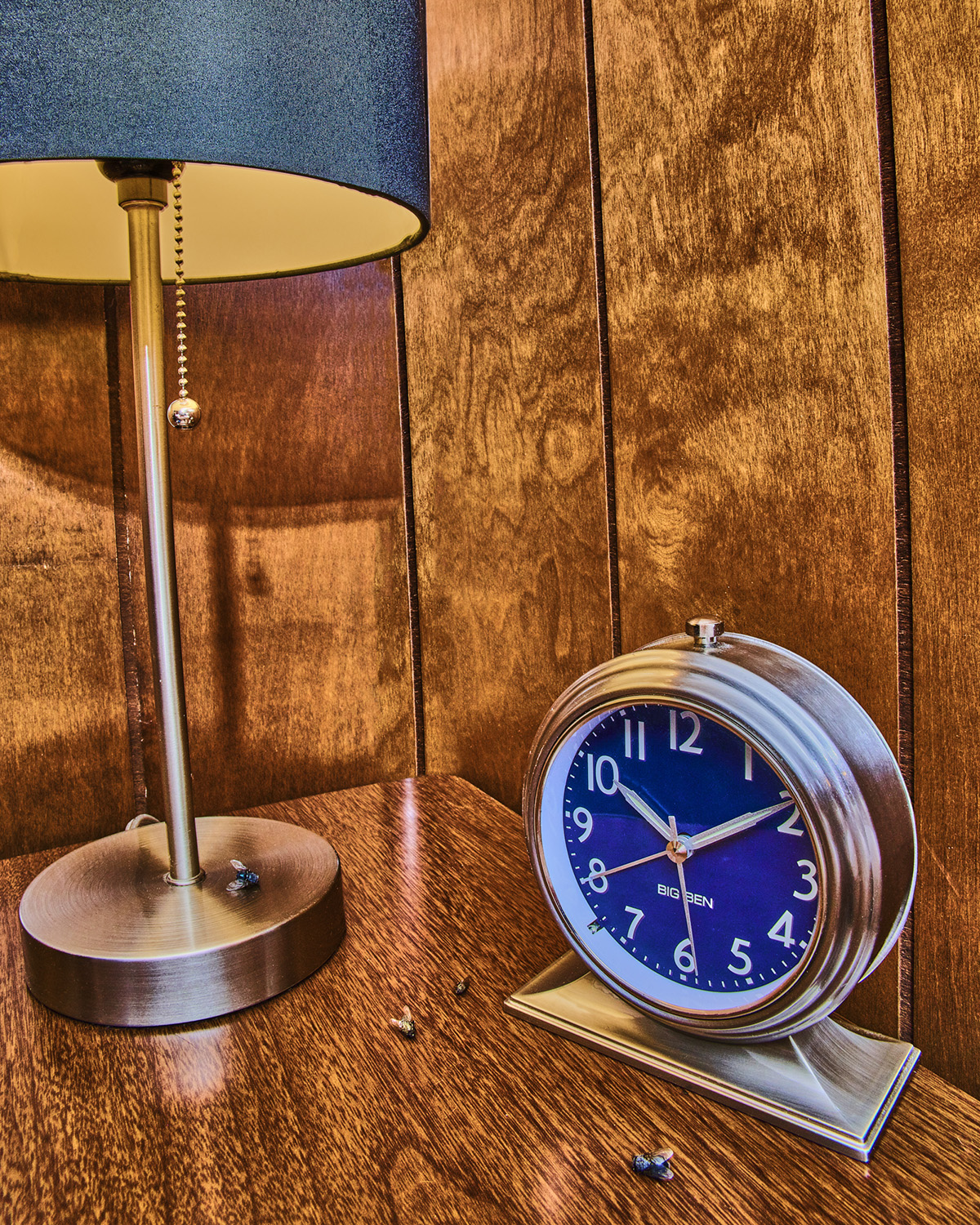 A table lamp and clock sit on a wooden surface.
