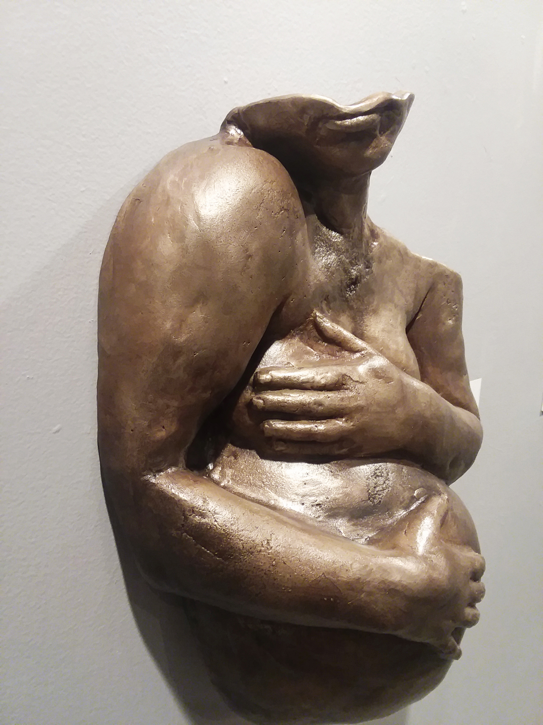 A bronze sculpture of a person holding their chest and stomach.