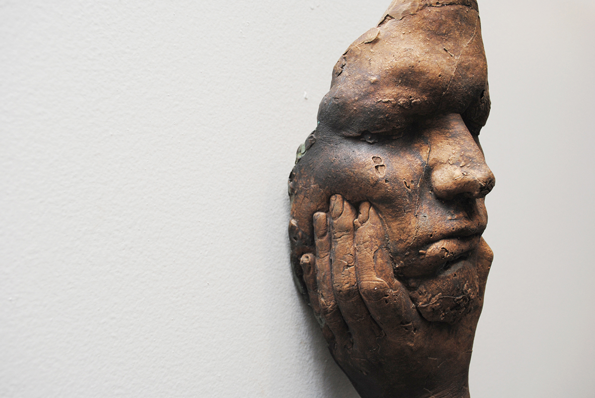 A found object sculpture of a hand pressing in a face.